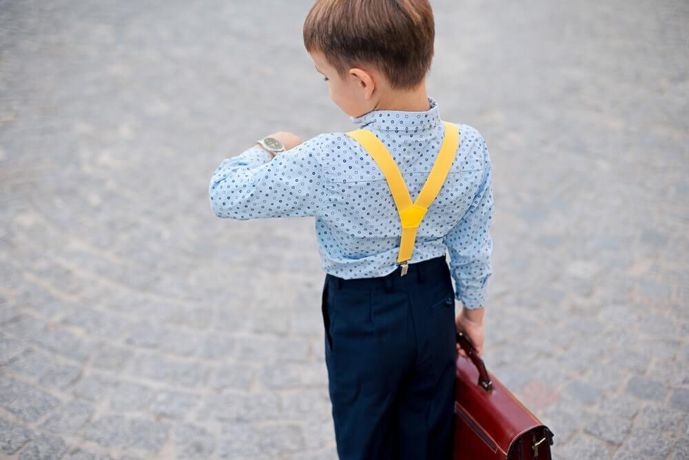 Chlapec kontroluje čas na dětských hodinkách