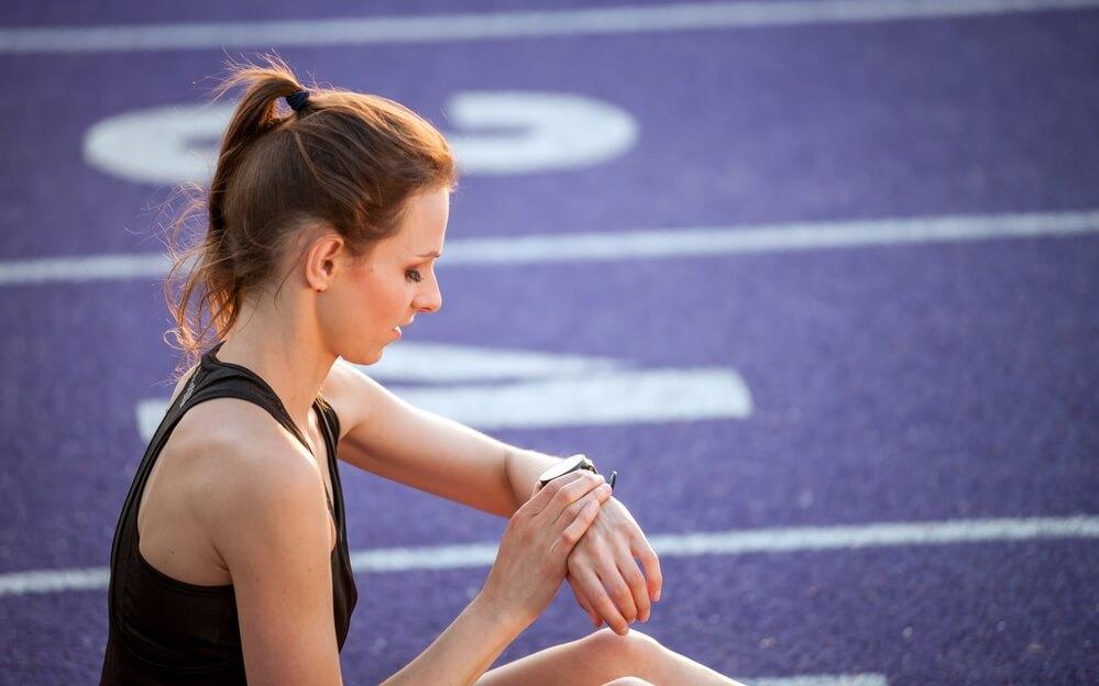 Mladá žena sedí na běžecké dráze a dívá se na sportovní hodinky