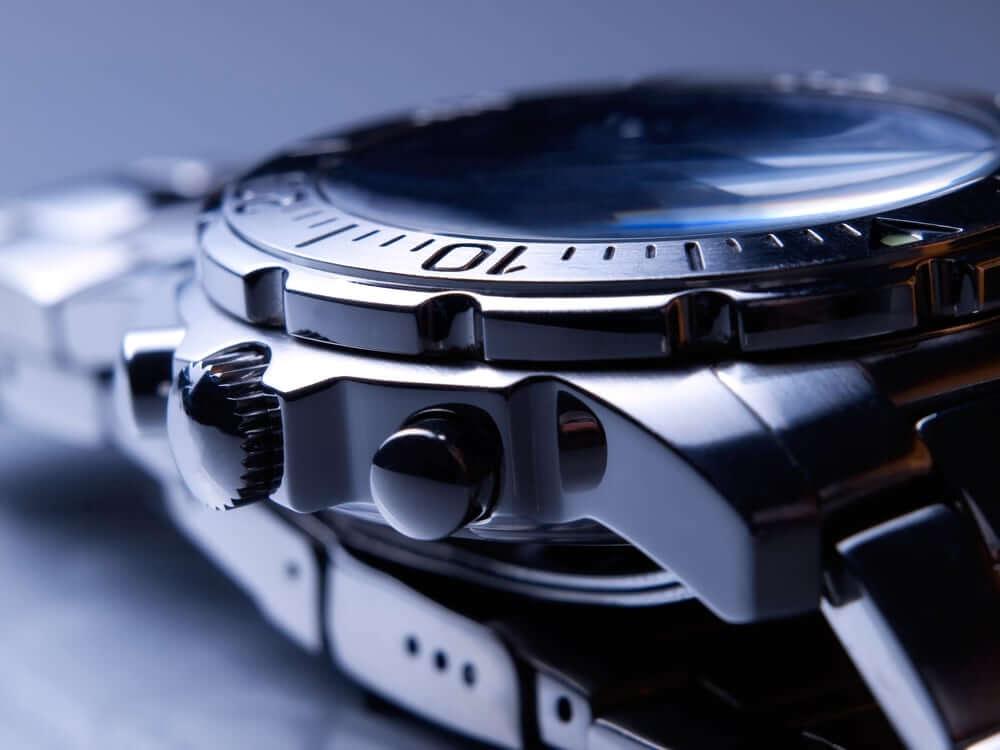 Detailní záběr na ocelové náramkové hodinky.